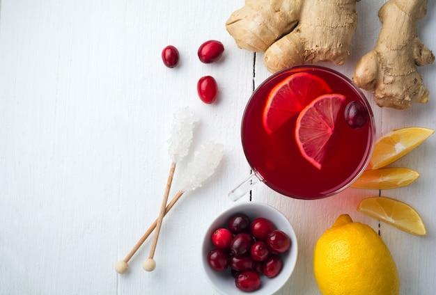 Свежий клюквенный сок с лимоном, ягодами, имбирем и сахаром на светлой поверхности. вид сверху. место для текста. выборочный фокус.