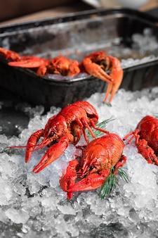 검은 접시 배경에 신선한 가재 음식입니다. 레스토랑 미식 건강식에서 허브 향신료 레몬 로즈마리와 얼음을 곁들인 붉은 가재 스낵 해산물 프리미엄 사진