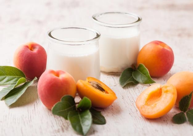 Fresh cream dessert with raw organic apricots on wooden board.