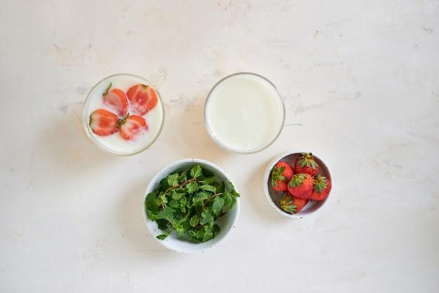 Свежий кремовый десерт с сырой органической клубникой на белой доске. йогурт во французском стиле