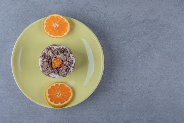 Muffin cremoso fresco con fette d'arancia sulla zolla gialla