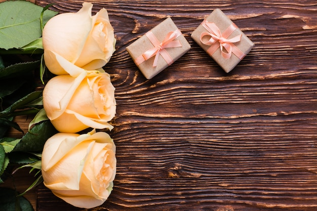 Fresh creamy roses and two packaged gifts on wood, top view