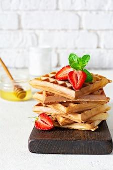 明るい背景に朝食に熟したイチゴ、ミント、蜂蜜と新鮮なさわやかなベルギーワッフル。