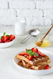 Свежие хрустящие бельгийские вафли со спелой клубникой, мятой и медом на завтрак