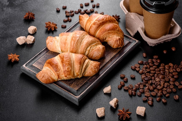 어두운 콘크리트 배경에 향기로운 커피 한잔과 함께 신선한 선명하고 맛있는 프랑스 크로. 상쾌한 아침 식사