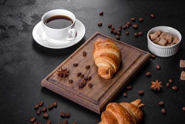 Свежий хрустящий вкусный французский круассан с чашкой ароматного кофе на темном фоне бетона. бодрящий завтрак