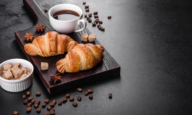 暗いコンクリートの背景に香りのよいコーヒーのカップと新鮮なさわやかなおいしいフレンチクロワッサン。爽快な朝食