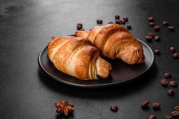 Свежий хрустящий вкусный французский круассан с кофейными зернами на черном столе