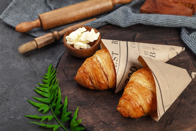 Fresh crispy baked croissants and butter on wooden board