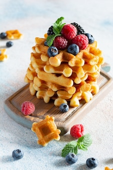 明るい背景の木の板に熟したベリー(ラズベリー、ブルーベリー、ブラックベリー)、ミント、粉砂糖を添えた朝食用の新鮮なクリスピーなベルギーワッフル。