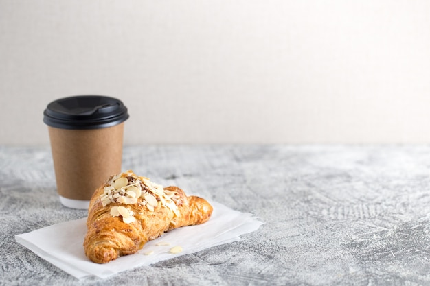 Fresh croissant and coffee in a paper cup on light/