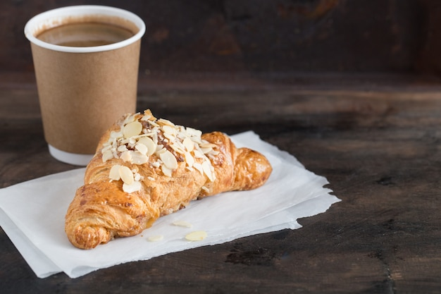 Fresh croissant and coffee in a paper cup