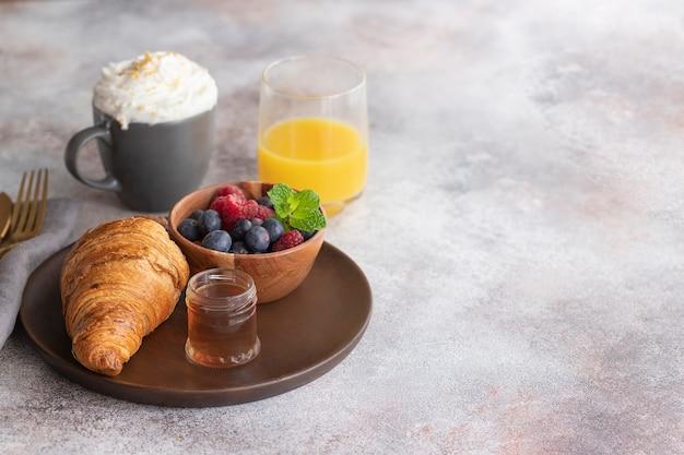Свежий круассан, кофе с молоком, фрукты, сироп и апельсиновый сок. континентальный завтрак.