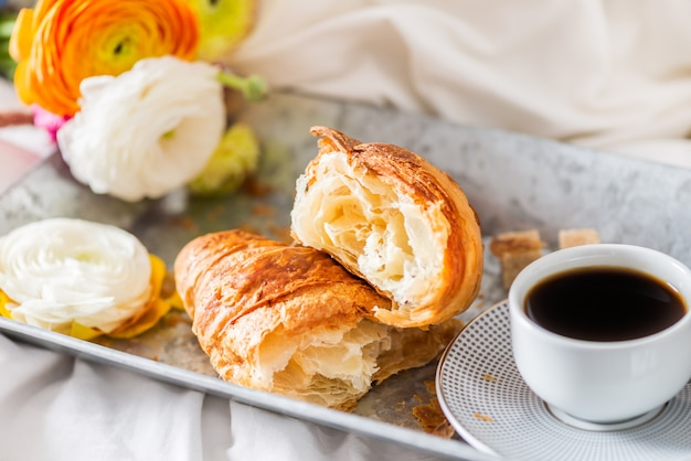 Fresh croissant, cup of coffee and ranunculus flowers. breakfast