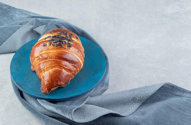 Croissant fresco decorato con gocce di cioccolato su tavola blu.