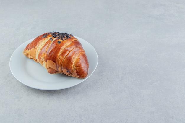 Croissant fresco decorato con cioccolato a goccia su piatto bianco.