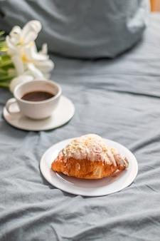 白いガラスプレートに新鮮なクロワッサンとベッドの上のコーヒーカップ。白いチューリップの花束。ベッドでの朝食。