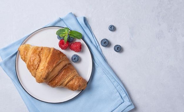 白い皿と青い背景に果実と青いナプキンに新鮮なクロワッサン。