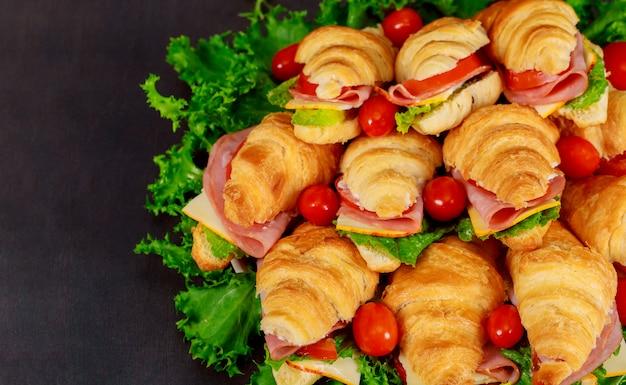 Свежий круассан или бутерброд с салатом, ветчиной, хамоном, помидорами на деревянном фоне