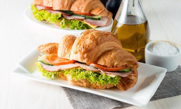 Свежий круассан или бутерброд с салатом, ветчиной на деревянных фоне.