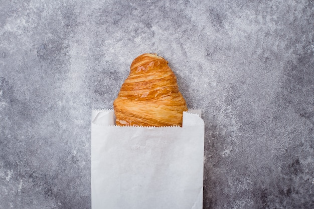 Fresh croissant on paper packaging on gray stone table background.