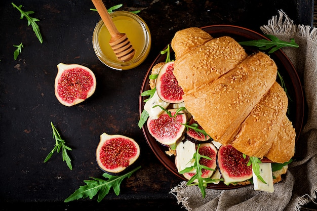 Fresh croissant sandwich with  brie cheese arugula and figs. delicious breakfast.