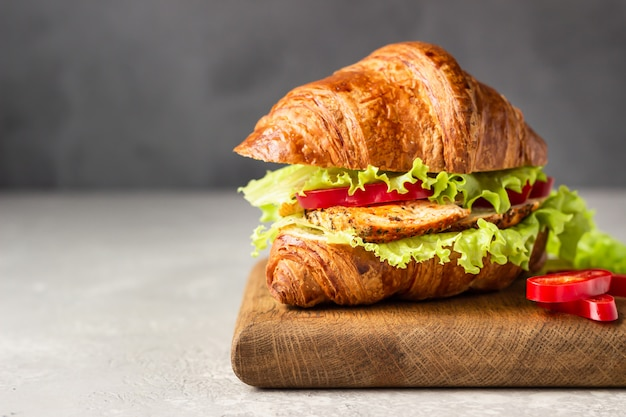 Fresh croissant sandwich with chicken, bell pepper, sauce and salad leaves on wooden board