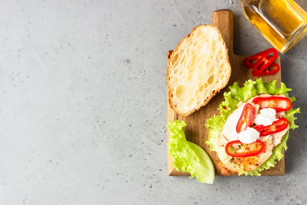 Fresh croissant sandwich with grilled chicken, bell pepper, sauce and salad leaves with juice