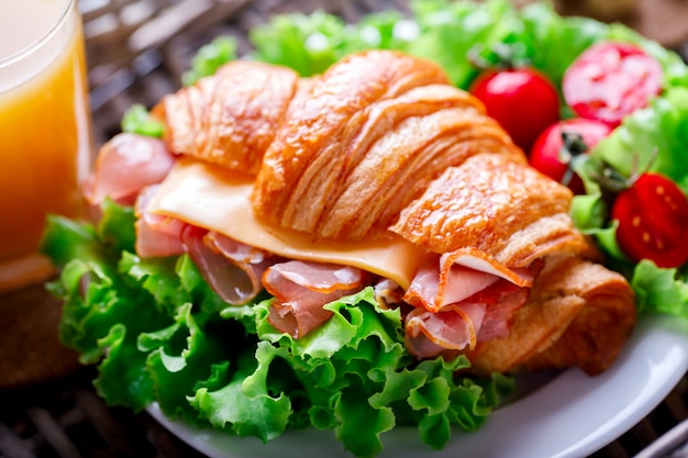 Fresh croissant sandwich with  ham, cheese,cherry tomatoes