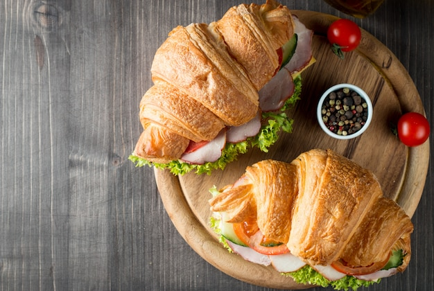 Fresh croissant or sandwich with salad, ham on wooden background.