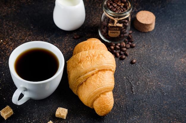 Свежий круассан с кружкой я черного кофе и кофейных зерен на темном фоне бетона. концепция горячих напитков, бодрящий завтрак.