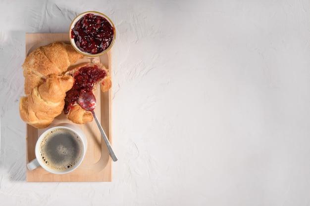 木の板にチェリージャム、灰色の石のテーブルにコーヒーのキャップが付いた焼きたてのクロワッサン