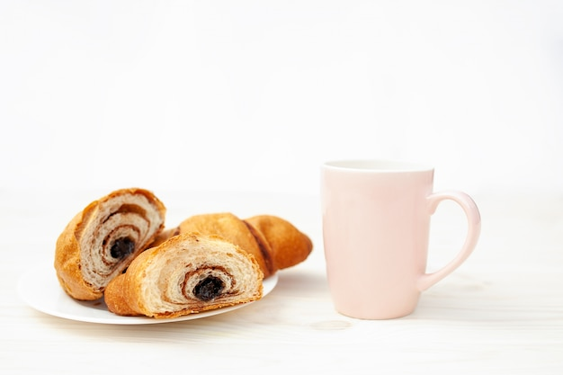 Fresh croissant with chocolate on the white wooden background