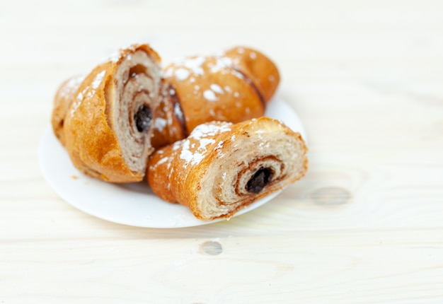 Fresh croissant with chocolate on the white wooden table