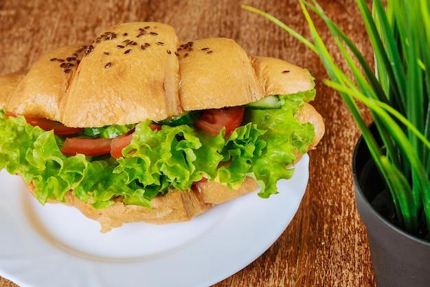 카페의 나무 테이블에 햄과 상추를 넣은 신선한 크루아상. 야채 크루아상