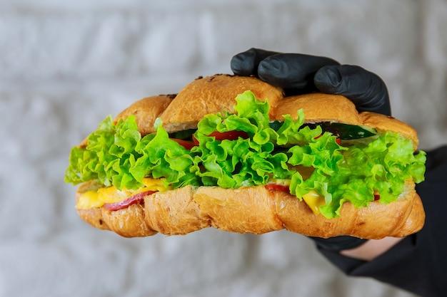 黒い手袋をはめたウェイターの手にハムとサラダを添えた焼きたてのクロワッサン