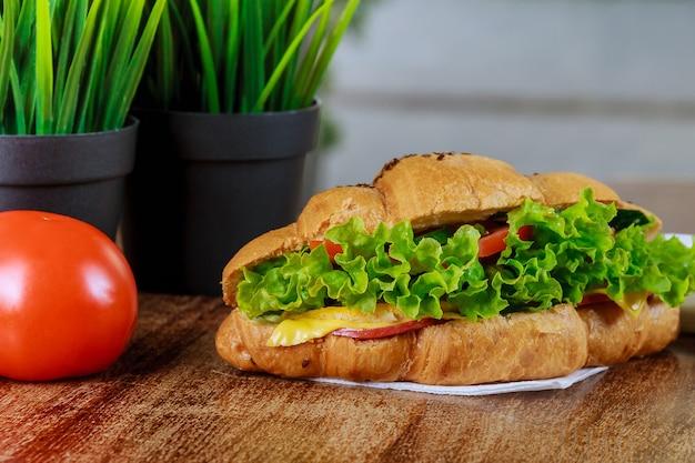 웨이터의 손에 햄과 샐러드가 있는 신선한 크루아상.