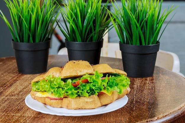 나무 테이블에 신선한 샐러드와 햄과 샐러드 잎을 곁들인 신선한 크루아상.