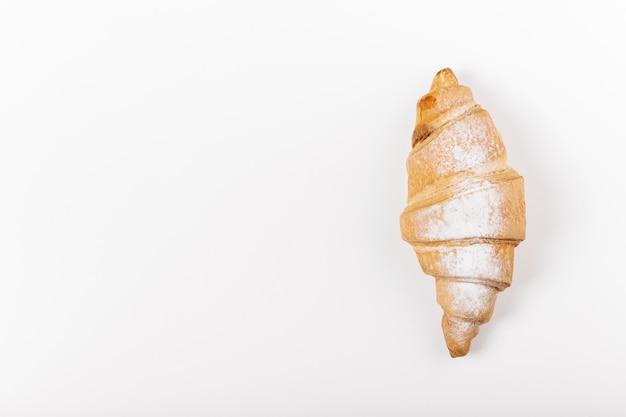 Fresh croissant with powder on white.