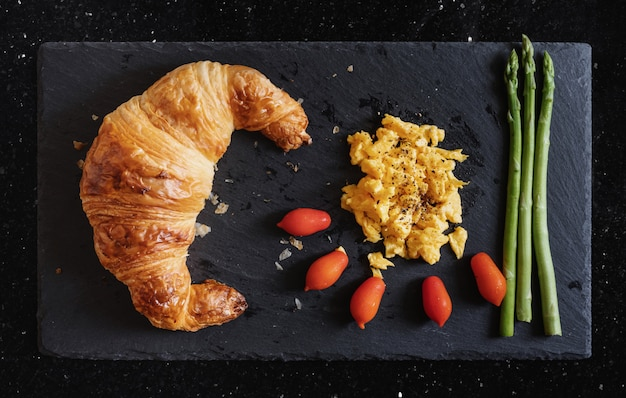Fresh croissant with scrambled eggs, cherry tomatoes and asparagus on black stone plate