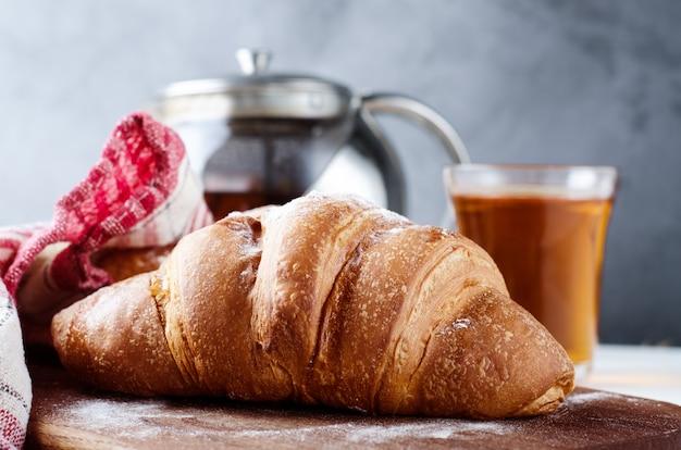 朝食に紅茶と焼きたてのクロワッサン。食品写真の背景。