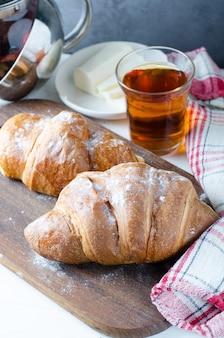 朝食に紅茶と焼きたてのクロワッサン。食べ物の写真。