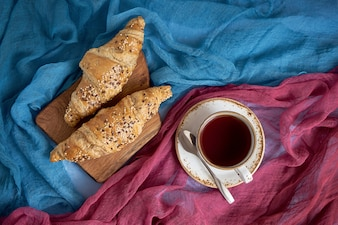 Fresh croissants and cup of black tea on colorful background.