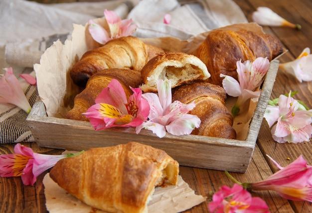 木製のテーブルのトレイに焼きたてのクロワッサンと花をクローズアップ
