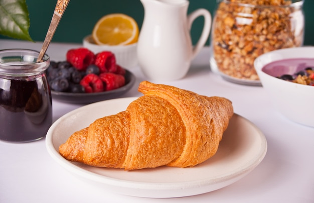 Свежие круассаны, булочки, ягоды, варенье из черной смородины и смузи. концепция завтрака.