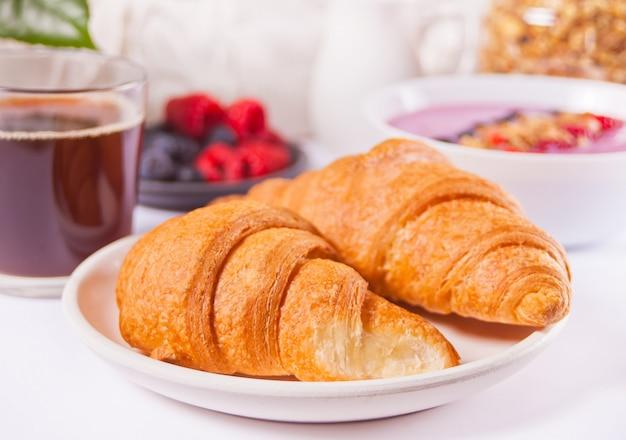 Свежие круассаны, булочки, ягоды, варенье из черной смородины, смузи. концепция завтрака.