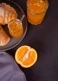 신선한 크루아상 빵, 오렌지, 오렌지 잼. 아침 식사 개념입니다. 평면도. 공간 복사