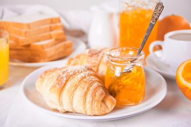 Свежие круассаны, булочки, апельсины, апельсиновый джем. концепция завтрака.