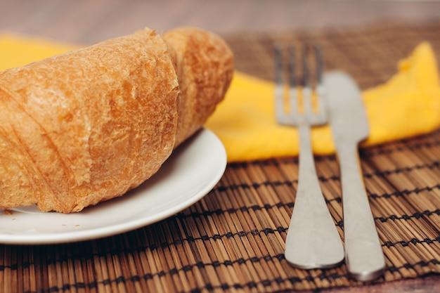 デザートのクローズアップのためのテーブルの朝食の焼きたてのクロワッサン