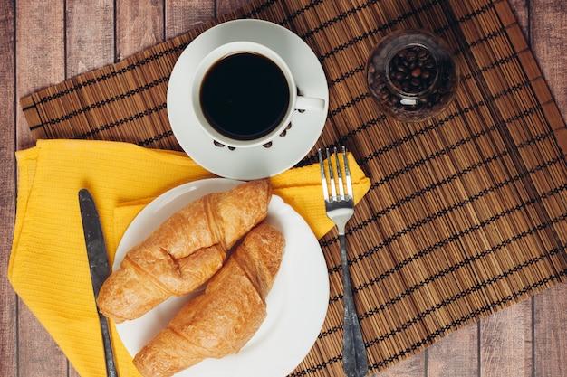 テーブルの上の焼きたてのクロワッサンコーヒーカップ朝食の食事